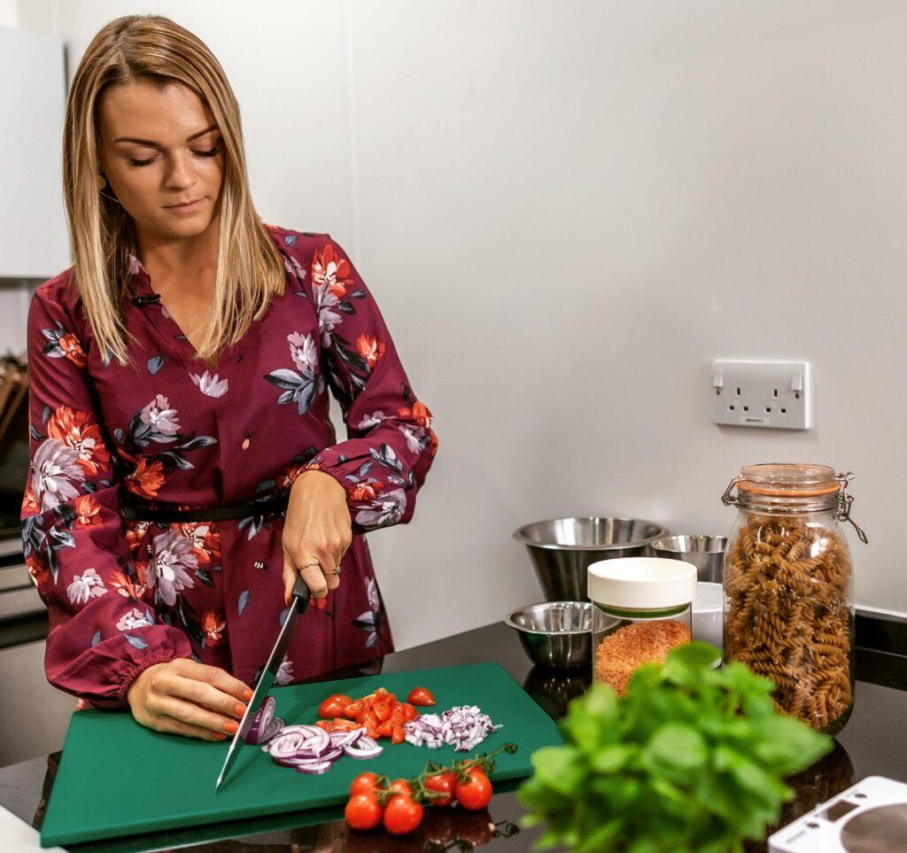 Nutritionist Hannah Baugh cutting vegetables on a kitchen worktop