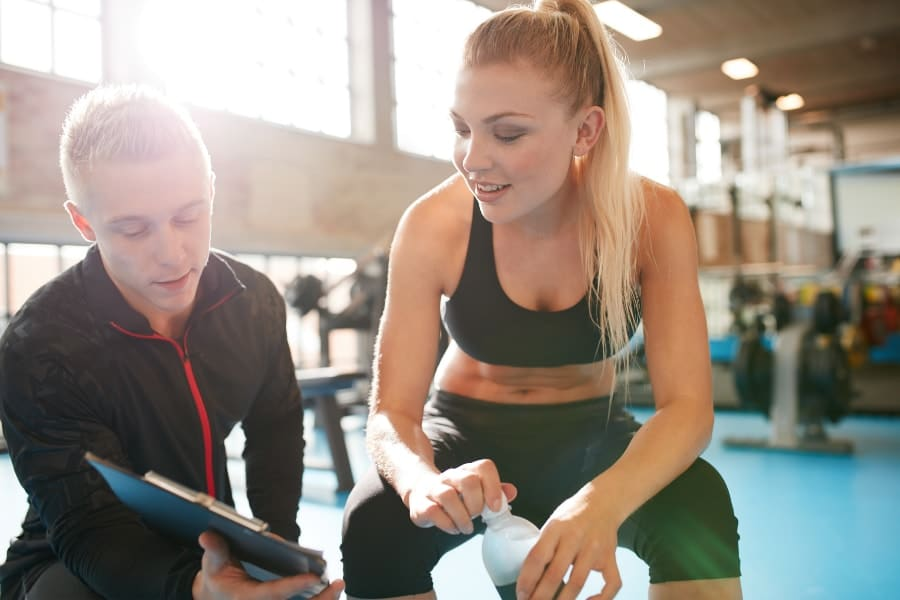 Personal trainer chatting and discussing training plan with client during a workout in the gym.