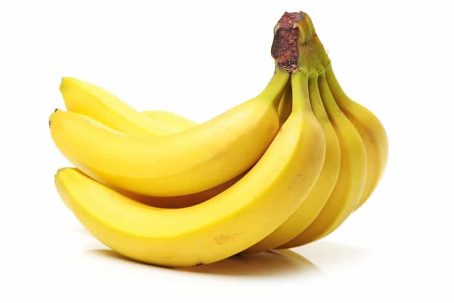 Mood Boosting foods A bunch of ripe yellow bananas on a white background