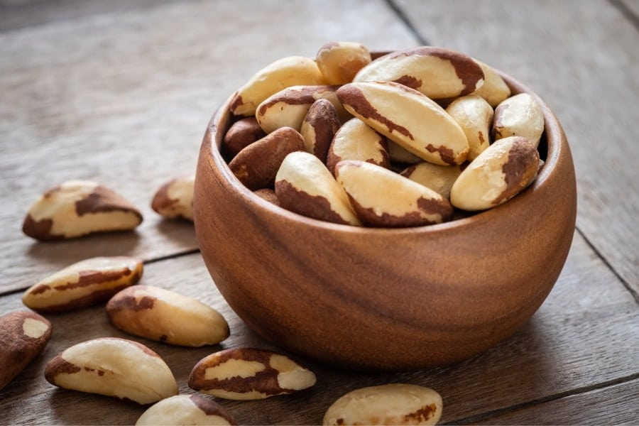 Mood Boosting foods Whole brazil nuts in wooden bowl with some loose brazil nuts scattered on the table