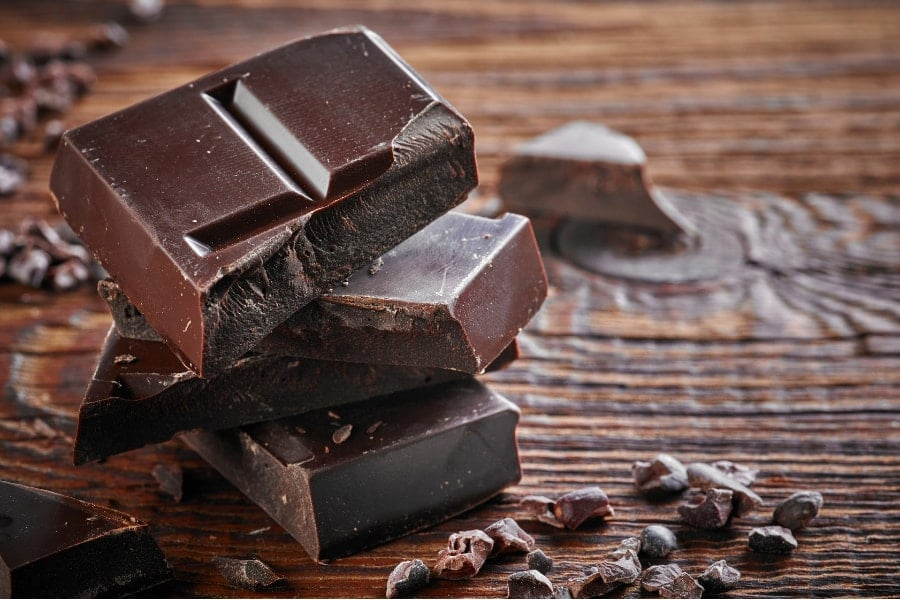 Mood Boosting foods Squares of dark chocolate on a brown table which is a great mood boosting food