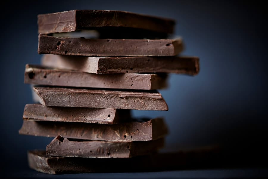 Mood Boosting Foods including dark chocolate stacked in pile with dark blue background