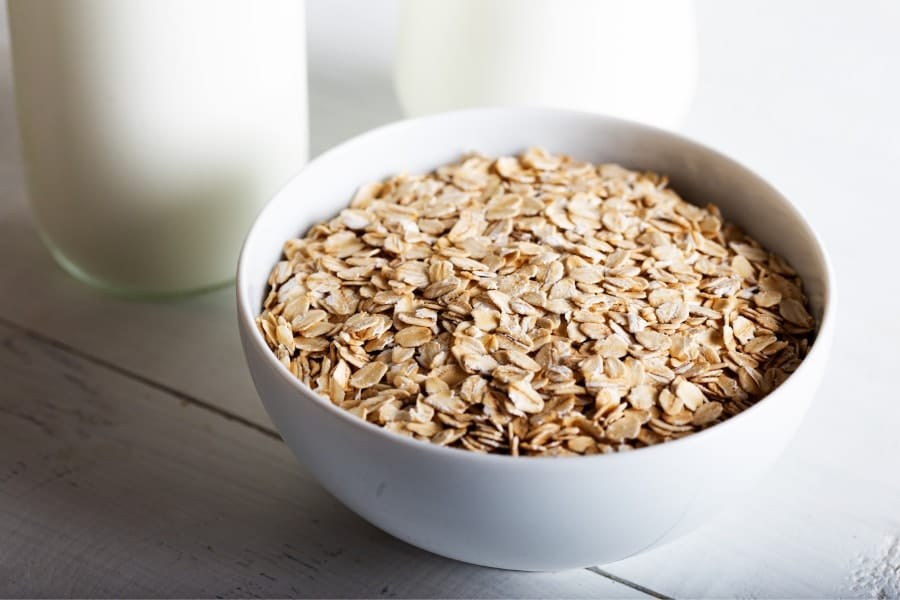 Mood Boosting foods a small white bowl full of oats with a close up of a pint of milk in the background