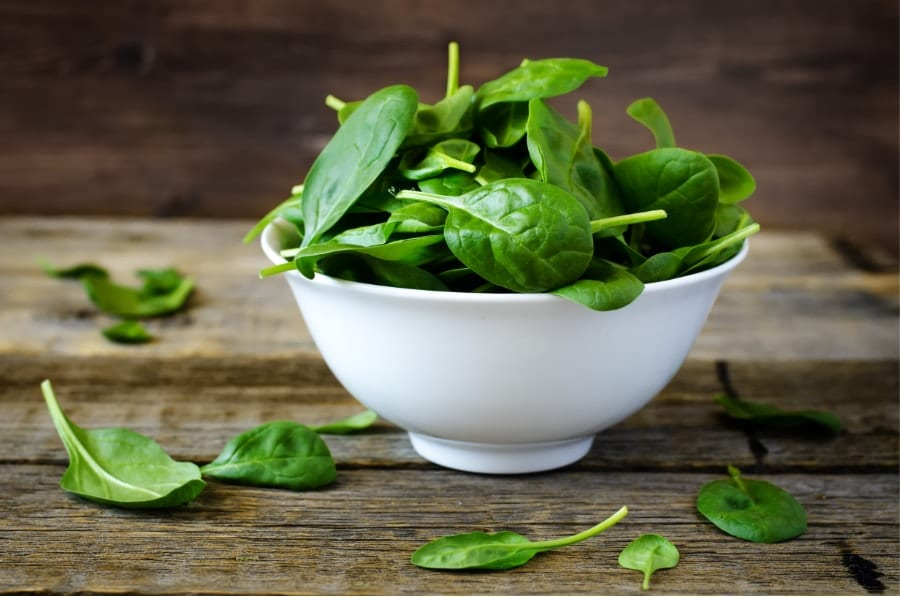 Mood Boosting foods Spinach leaves in a wide dish on a table with some spinach leaves on the table