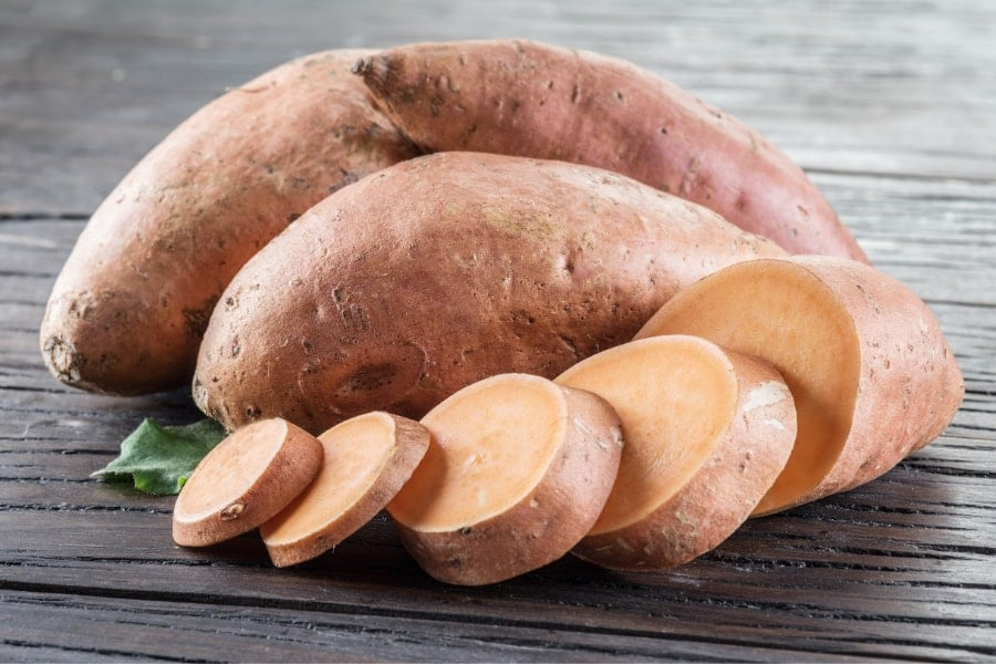 Mood Boosting foods Close up up of 2 uncooked sweet potatoes and one sliced seet potato on brown wooden table