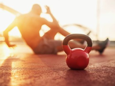 Kettle bell in focus, a man in background doing personal fitness training in the early morning at sunrise.